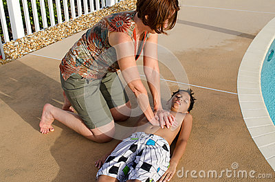 Woman performing cpr on a child by a pool