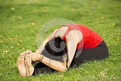 Woman Performs Deep Forward Bend in Park