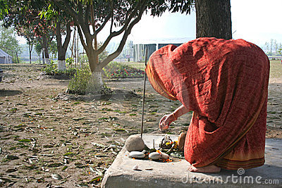 Woman performs traditional morning worship ritual in courtyard