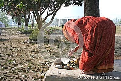 Woman performs traditional morning worship ritual in courtyard