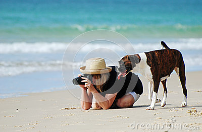Woman & pet dog on tropical beach taking photos