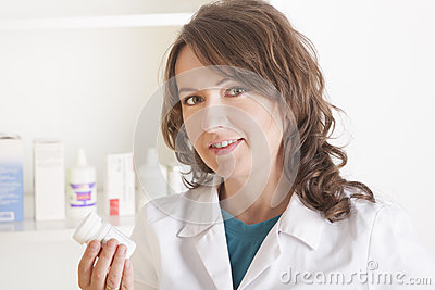 Woman pharmacist with a bottle of drugs
