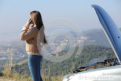 Woman on the phone beside a breakdown car