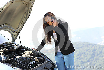 Woman on the phone looking a breakdown car