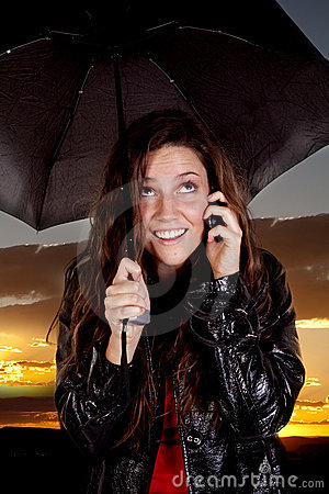 Woman on phone under umbrella