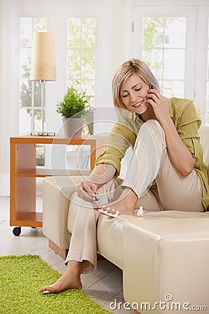 Woman on phone using nail polish