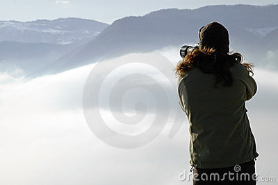 Woman photographing above clouds