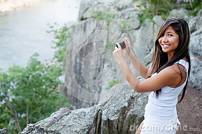 Woman photographing scenic river