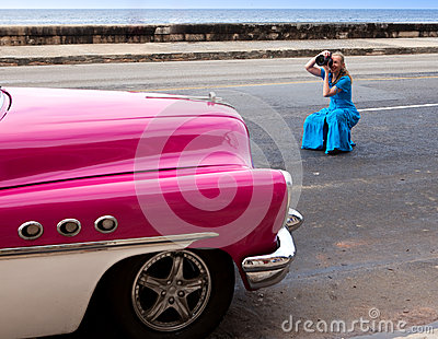 The woman photographs the ancient car on the Malecon street January 27, 2013 in Old  Havana, Cuba