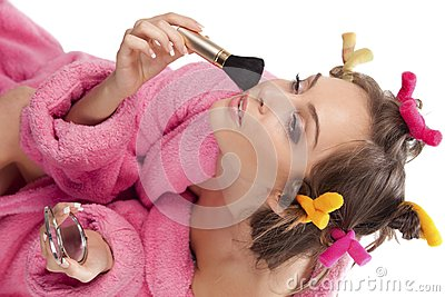 Woman in pink bath robe making-up
