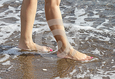 Woman with pink nailpolish walking on the beach