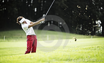 Woman pitching at golf course.