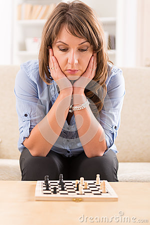 Woman playing chess at home
