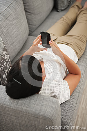 Woman playing on couch with mobile
