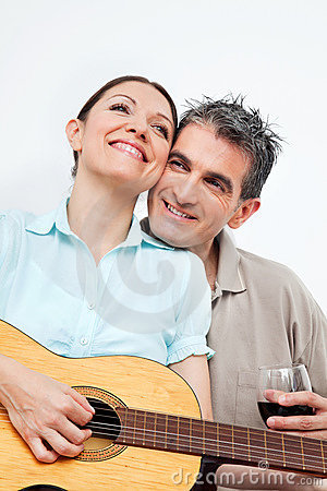 Woman playing guitar for man