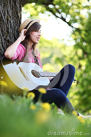 Woman playing guitar in park