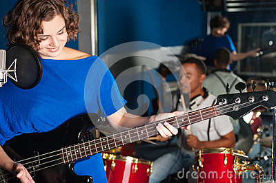 Woman playing guitar in recording studio