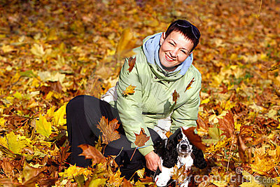 Woman playing with her dog  in autumn park