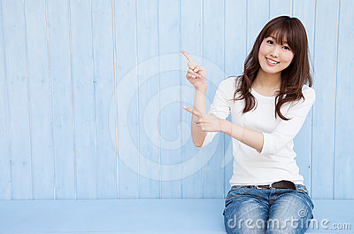 Woman pointing at a blue background