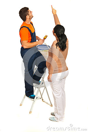 Woman  pointing to  painter on wall
