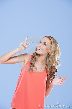 Woman pointing upwards to blank copyspace