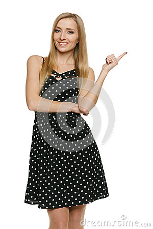 Woman in polka dot dress pointing at empty copy space