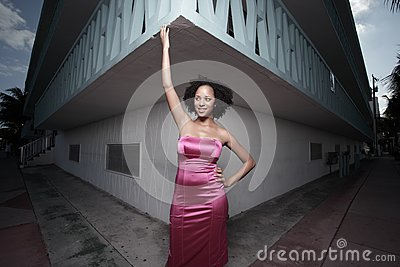 Woman posing by a building