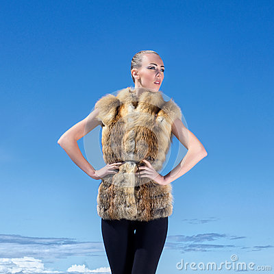 A woman posing in a fur jacket on a sky background