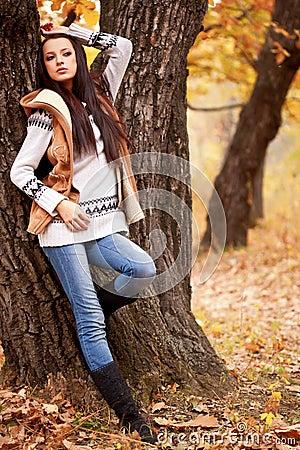 Woman posing near tree in autmn park