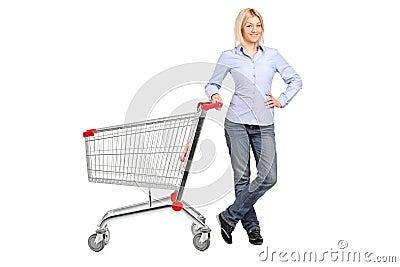 Woman posing next to an empty shopping cart