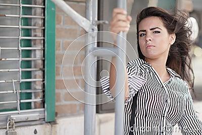 Woman posing by scaffolding