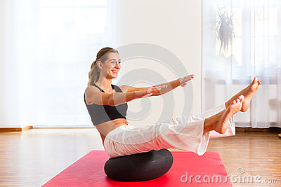 Woman practicing poses on exercise ball
