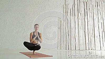 Woman practicing yoga - ardha baddha padma padangusthasana - balancing on toes. Young sporty woman practicing yoga in fitness studio - ardha baddha padma stock video
