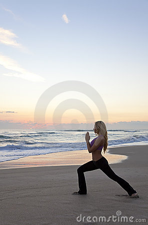 Woman Practicing Yoga on Beach Sunrise or Sunset