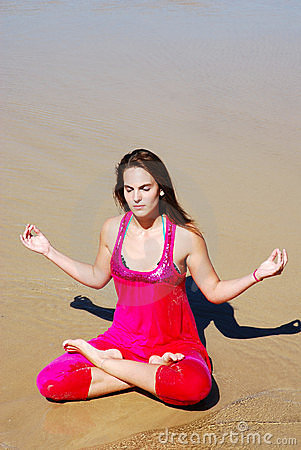 Woman practising yoga on beach