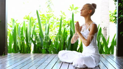 Woman practising yoga and meditating. On a deck in tropics stock video