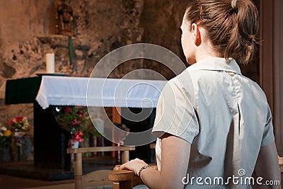 Woman praying at an alter