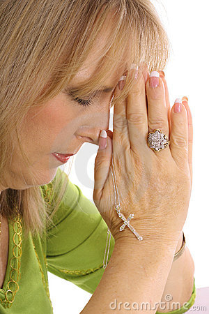 Woman praying with rhinestone cross upclose
