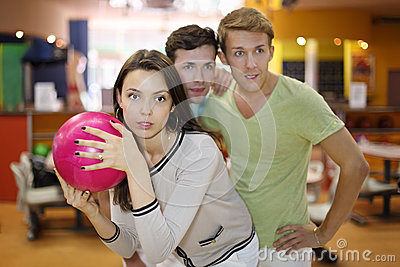 Woman prepares to throw of ball; men look