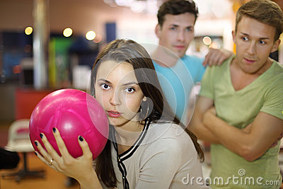 Woman prepares to throw of ball; men look at her