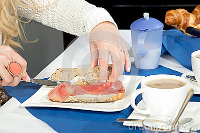 Woman preparing a roll and ham