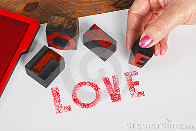 Woman printing LOVE using wooden letterpress