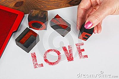 Woman printing LOVE using wooden letterpress