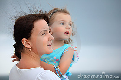 Woman protects girl from wind on seacoast