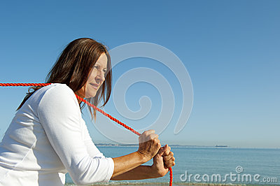 Woman pulling rope ocean background