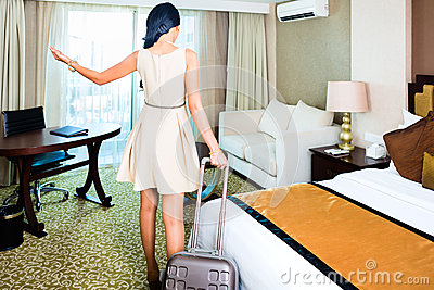 Woman pulling suitcase in hotel room