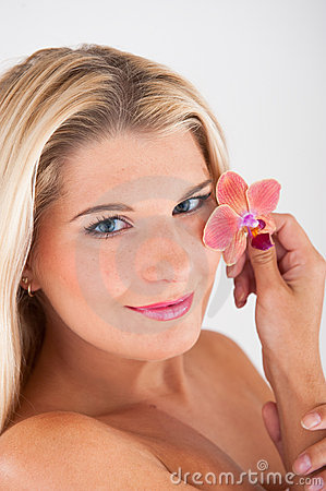 woman with a pure healthy skin holding an orchid
