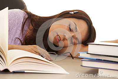 Woman purple shirt asleep pen in ear books