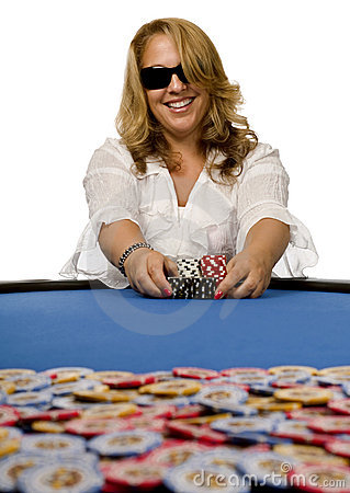 Woman pushes poker chips on blue felt table