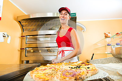 Woman pushing the finished pizza from the oven